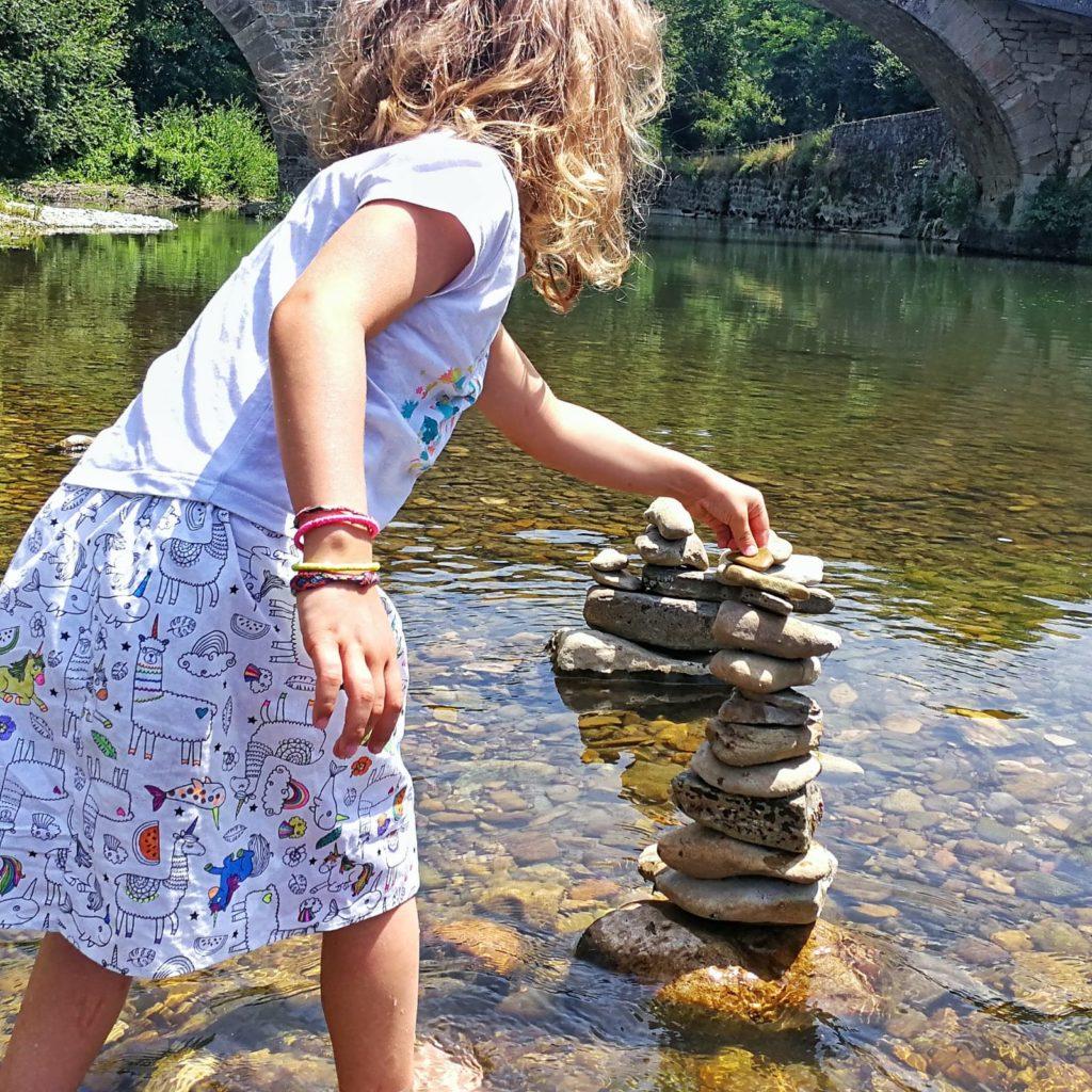 Petite fille jouant dans une riviere avec une jupe couture